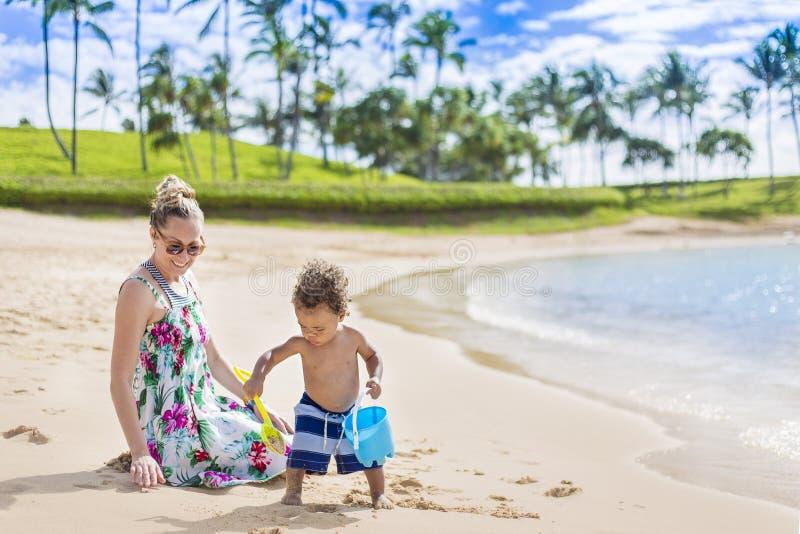 Leuke gemengde race weinig jongen die in het zand het strand met zijn moeder spelen stock foto