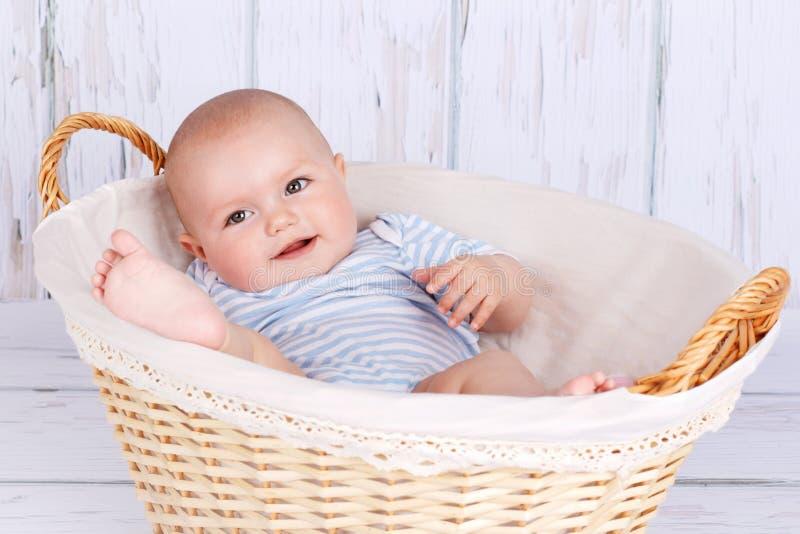 Leuke glimlachende baby die in rieten mand liggen stock fotografie