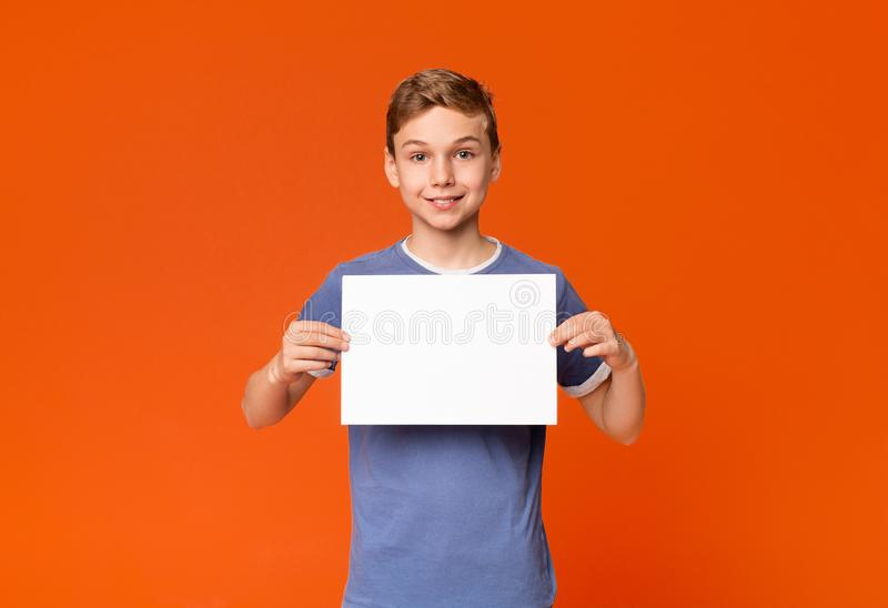 Leuke glimlachende jongen die wit leeg aanplakbiljet houden stock afbeeldingen