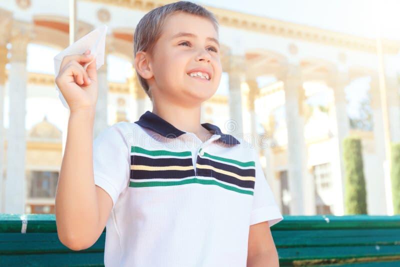 Leuke glimlachende jongen met document vliegtuig stock afbeeldingen