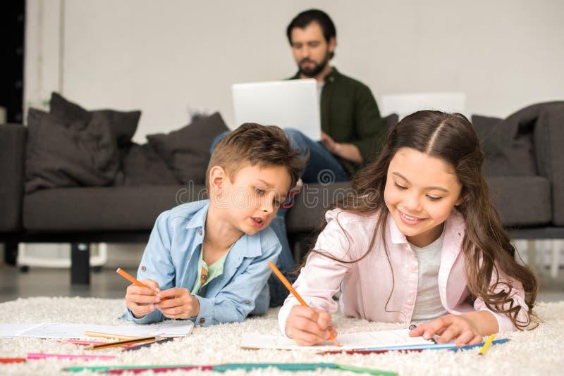 leuke glimlachende kinderen die op tapijt liggen en met kleurpotloden trekken terwijl vader die laptop met behulp van stock foto
