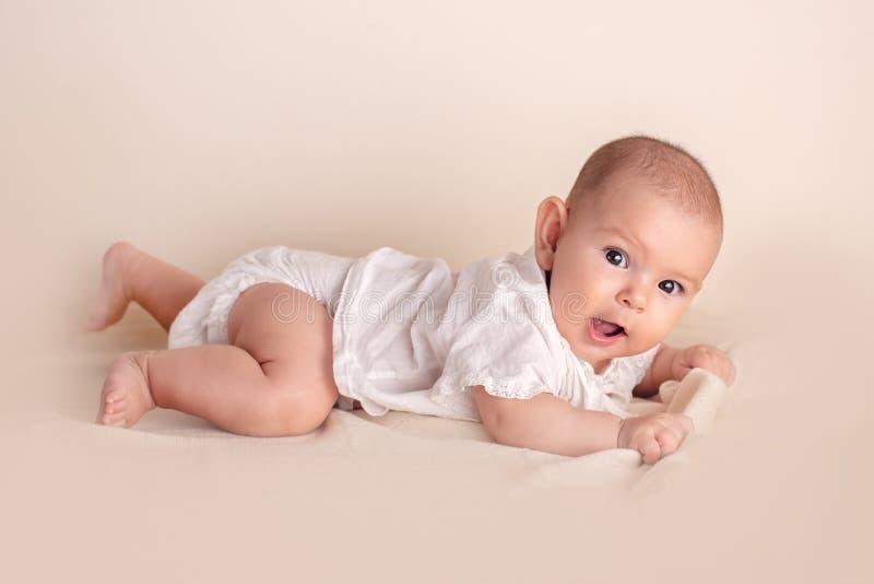 Leuke grappige baby met grote mooie ogen die op een witte deken liggen stock afbeeldingen