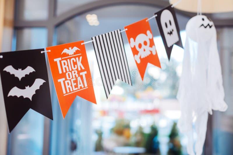 Leuke grappige en enge kleine vlaggen met schedels en knuppels die boven Halloween-lijst hangen royalty-vrije stock afbeelding