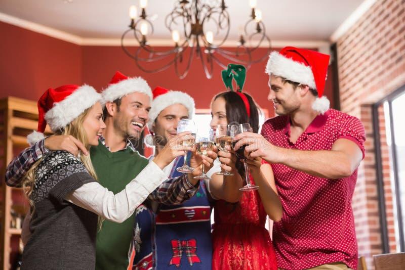 Leuke groep vrienden die met santahoeden roosteren stock foto's