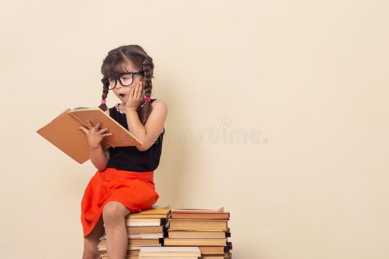 Leuke het boekzitting van de meisjelezing op stapel van boeken royalty-vrije stock foto