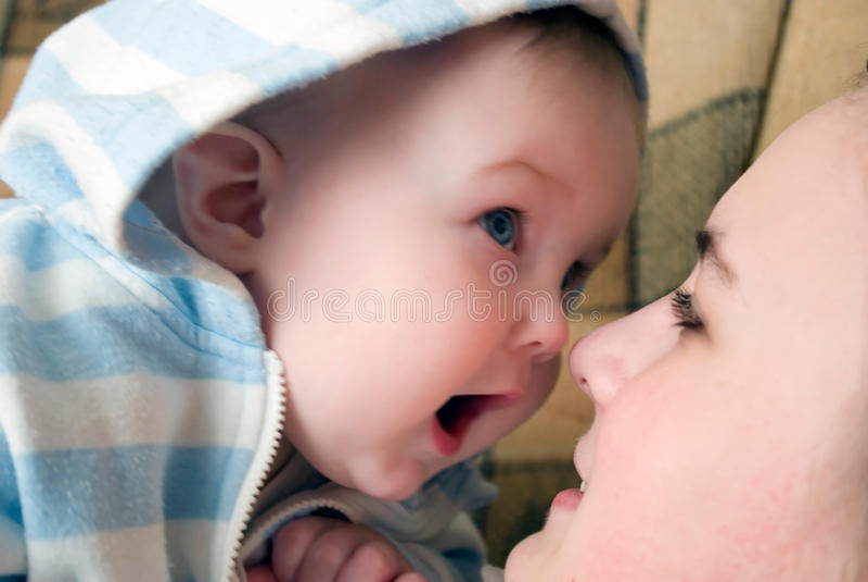 Leuke het glimlachen babyspelen met het houden van van moeder stock foto