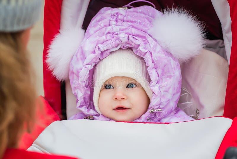 Leuke het glimlachen babyzitting in een wandelwagen stock foto's