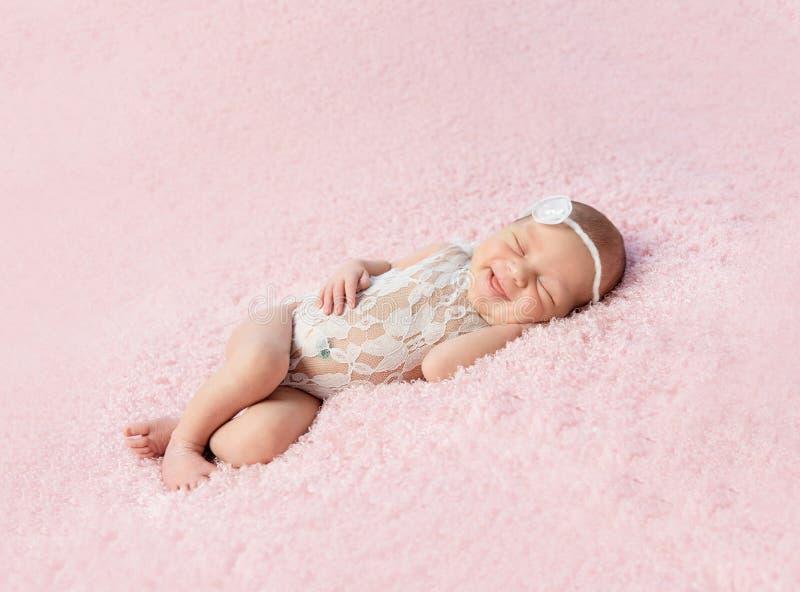 Leuke het glimlachen pasgeboren babyslaap op deken stock foto