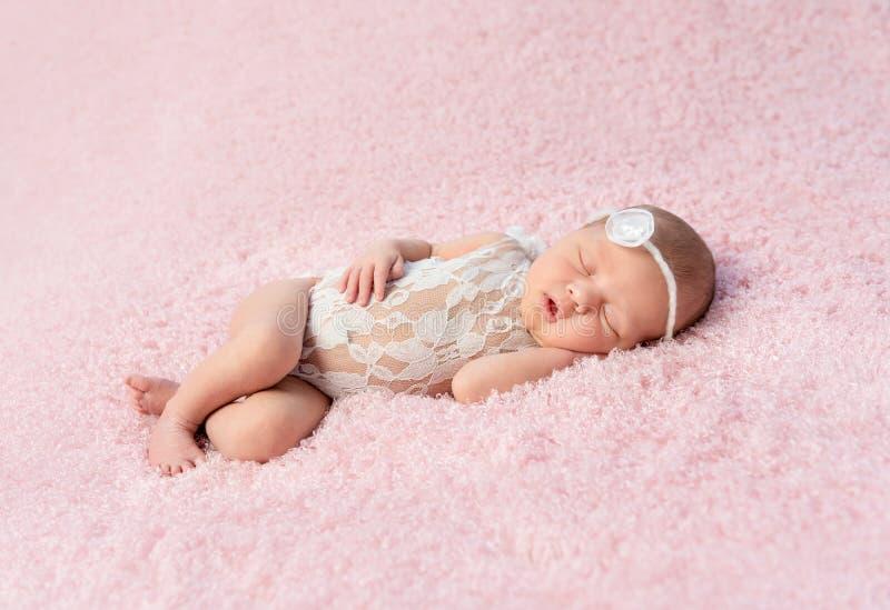 Leuke het glimlachen pasgeboren babyslaap op deken royalty-vrije stock fotografie