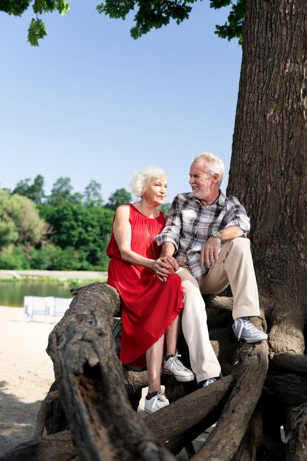 Leuke het houden van teruggetrokken paarzitting op grote boom dichtbij mooie rivier stock fotografie