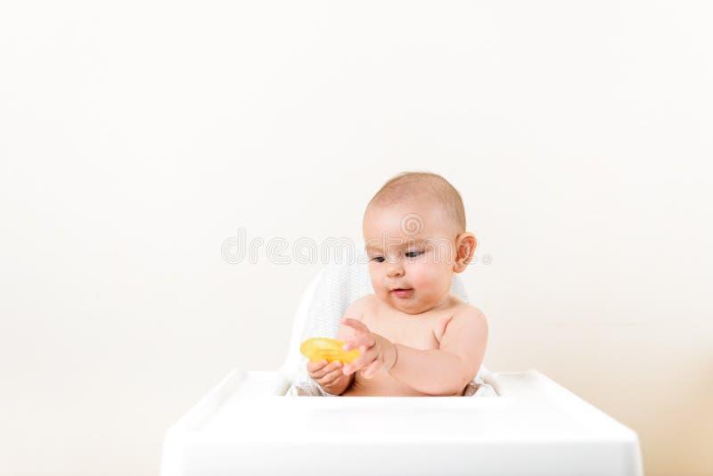 Leuke het jonge geitje van de babyzuigeling het bijten zitting in highchair en het kauwen gele eething stuk speelgoed exemplaar r royalty-vrije stock foto