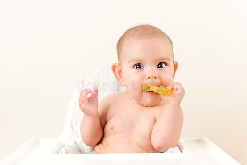 Leuke het jonge geitje van de babyzuigeling het bijten zitting in highchair en het kauwen gele eething stuk speelgoed exemplaar r royalty-vrije stock afbeelding