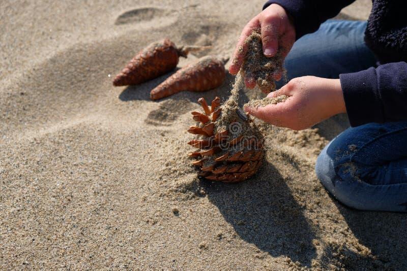 Leuke het meisjeshanden die van het Babykind met zand op zonnig strand spelen stock afbeeldingen