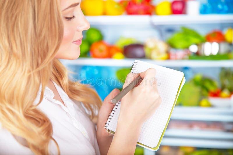 Leuke huisvrouw het schrijven lijst aan supermarkt royalty-vrije stock afbeeldingen