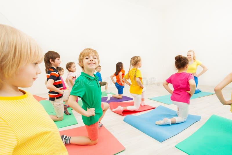 Leuke jong geitjejongen het praktizeren gymnastiek in gymnastiek stock foto's