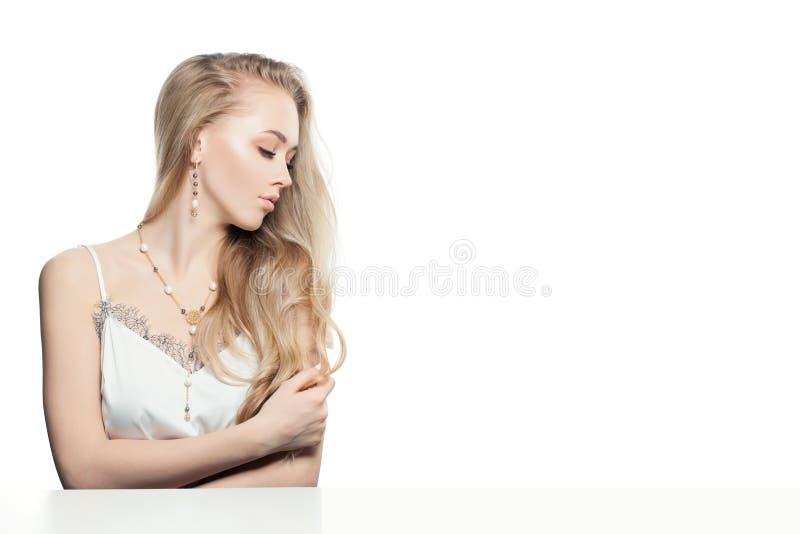 Leuke jonge blonde haarvrouw die gouden de kettingshalsband en oorringen van het juwelenjuweel met parels dragen die op witte ach royalty-vrije stock afbeelding