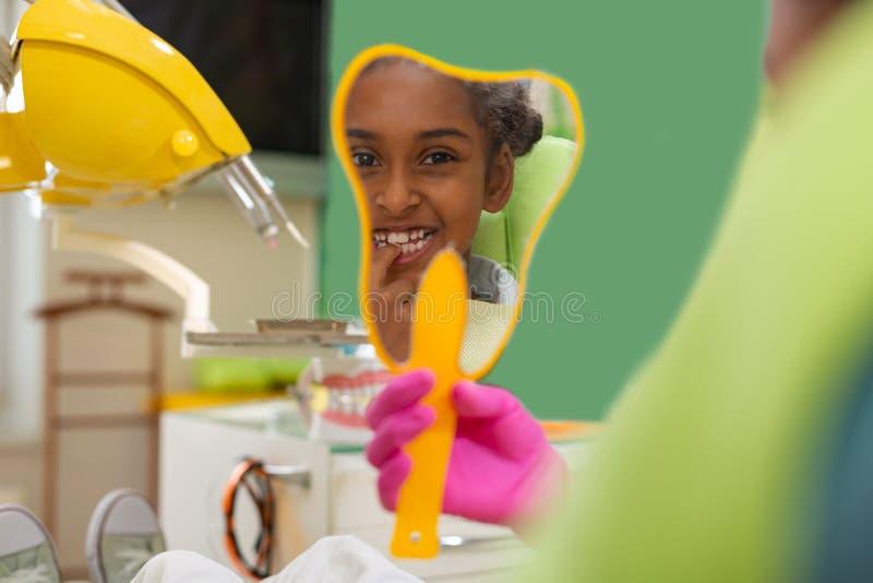 Leuke jonge donker-gevilde vrouwelijke patiënt die haar tanden bekijken stock afbeeldingen