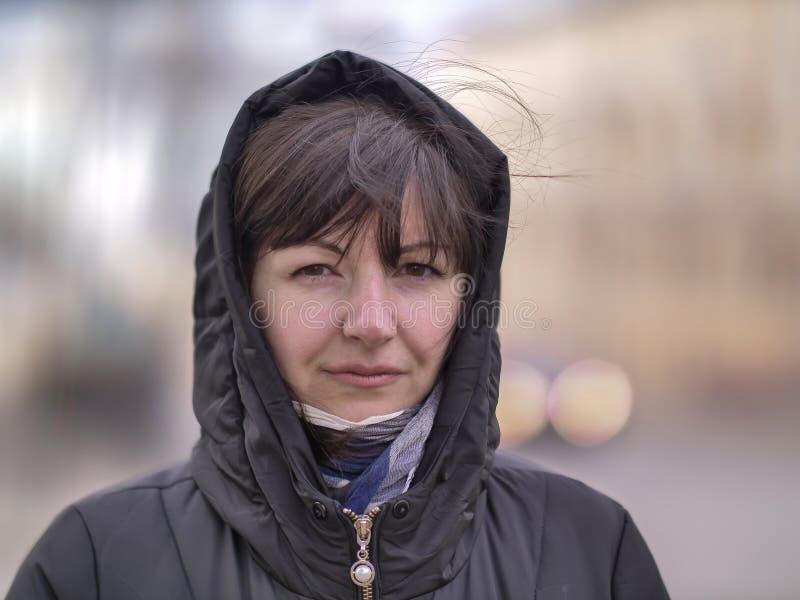 Leuke jonge donkerbruine vrouw in een kap op een stadsstraat die de camera onderzoeken stock afbeelding