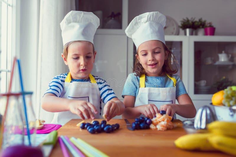 Leuke jonge geitjes die een fruitsalade in keuken voorbereiden stock afbeelding