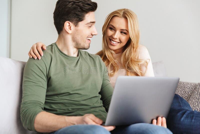 Leuke jonge het houden van paarzitting op bank die laptop computer met behulp van stock afbeeldingen
