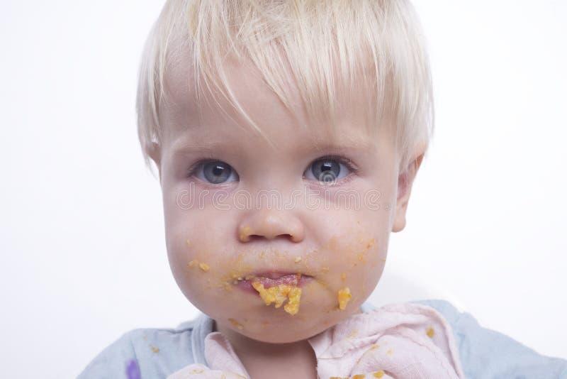 Leuke jonge jongen die met slordig gezicht eten royalty-vrije stock afbeelding