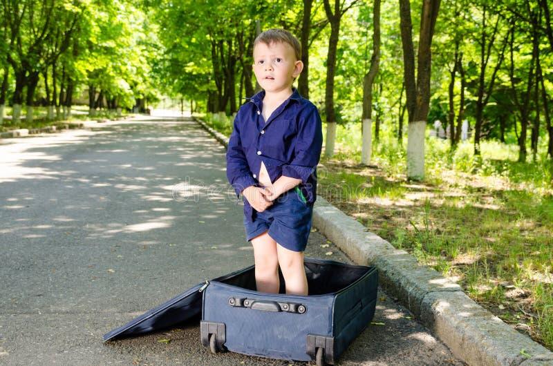 Leuke jonge jongen die zich in een open koffer bevinden stock afbeeldingen