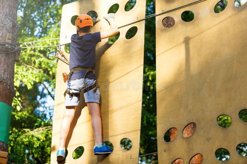 Leuke jonge jongen in helm met het beklimmen van materiaal in het kabelpretpark De zomerkamp, vakantie royalty-vrije stock foto's