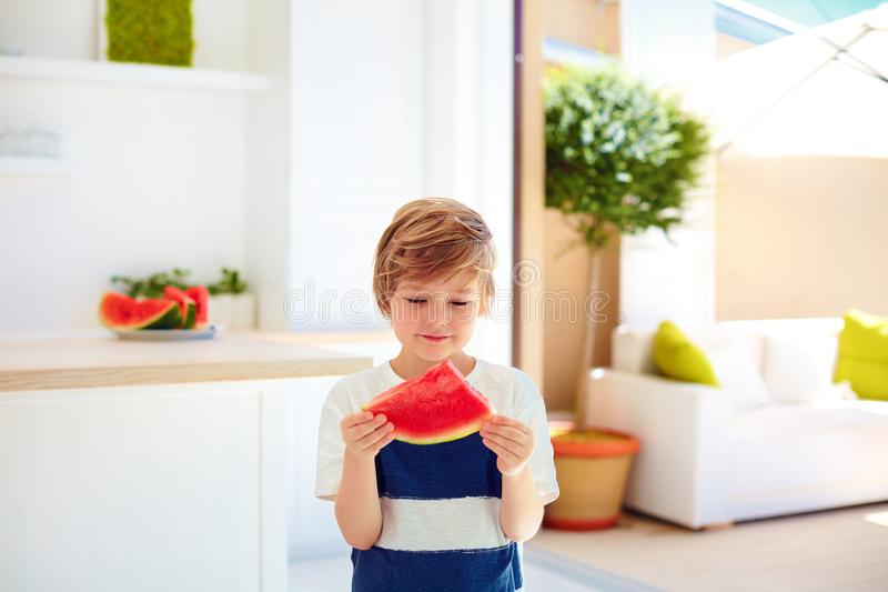 Leuke jonge jongen, jong geitje die een stuk van rijpe watermeloen thuis keuken eten royalty-vrije stock afbeelding