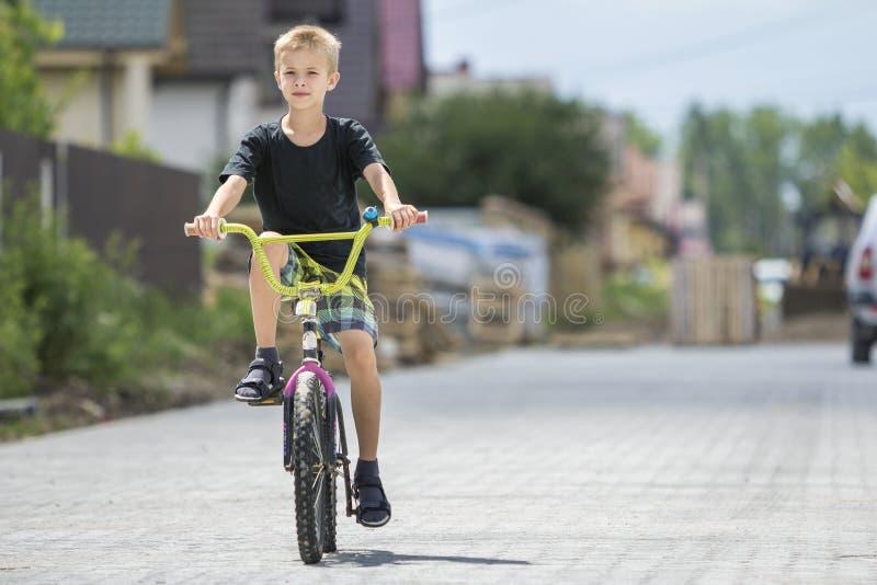 Leuke jonge knappe blonde jongen in toevallige berijdende het kindfiets van de de zomerkleding langs zonnige lege bedekte straat  stock foto