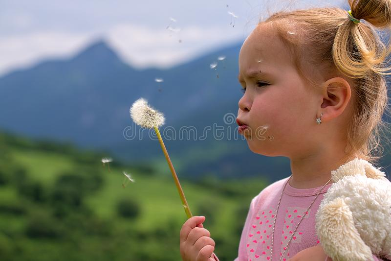 Leuke jonge meisje blazende paardebloem in zonnige dag stock afbeeldingen
