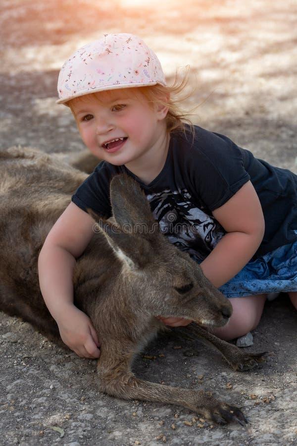 Leuke jonge meisje en kangoeroe in de dierentuin Weinig van het leeftijds 1-2 voer van het kindmeisje grijze kangoeroe in Isra?l royalty-vrije stock foto