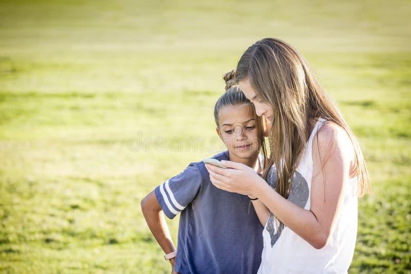 Leuke jonge meisjes die op virale sociale media video op mobiele celtelefoon in openlucht letten royalty-vrije stock fotografie