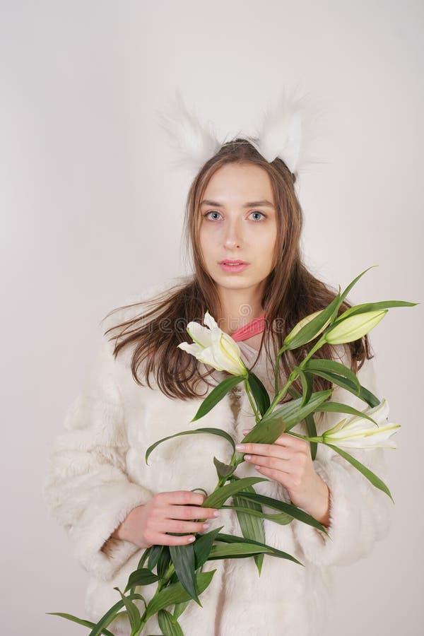 Leuke jonge tienermeisje status in een van de de winter warme bontjas en kat bontoren op haar hoofd, houdt zij een tak van verse  royalty-vrije stock foto