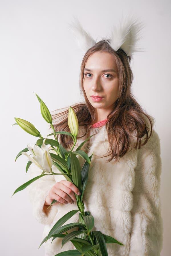 Leuke jonge tienermeisje status in een van de de winter warme bontjas en kat bontoren op haar hoofd, houdt zij een tak van verse  stock foto's