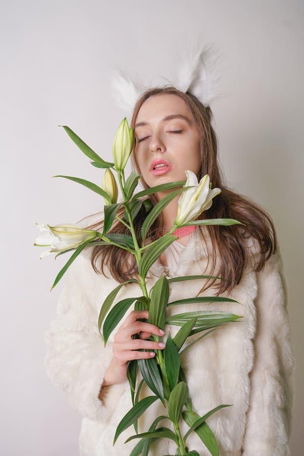 Leuke jonge tienermeisje status in een van de de winter warme bontjas en kat bontoren op haar hoofd, houdt zij een tak van verse  royalty-vrije stock afbeelding