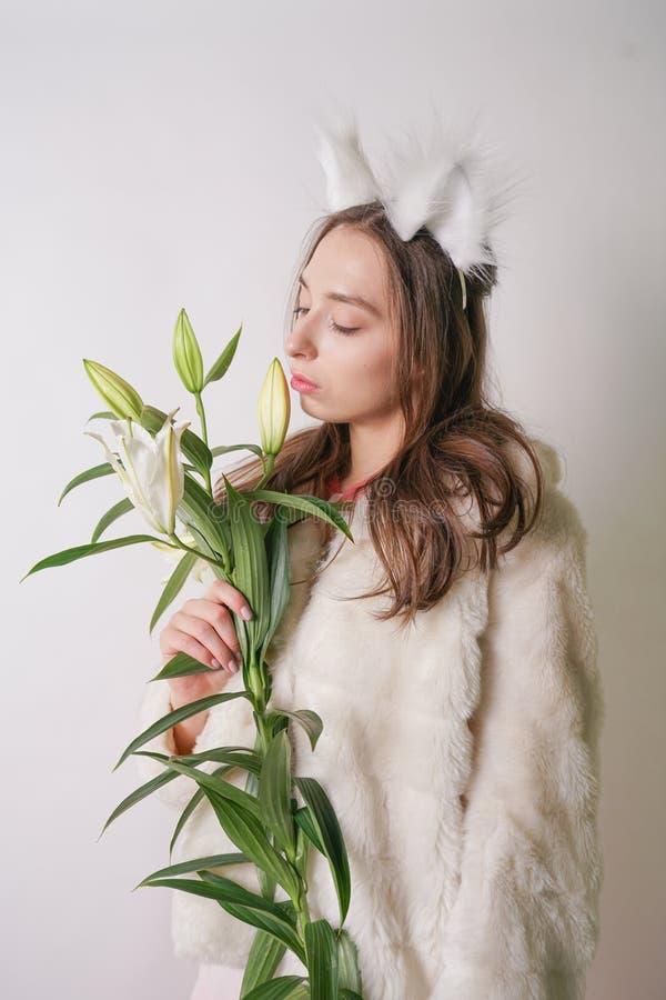 Leuke jonge tienermeisje status in een van de de winter warme bontjas en kat bontoren op haar hoofd, houdt zij een tak van verse  stock afbeelding
