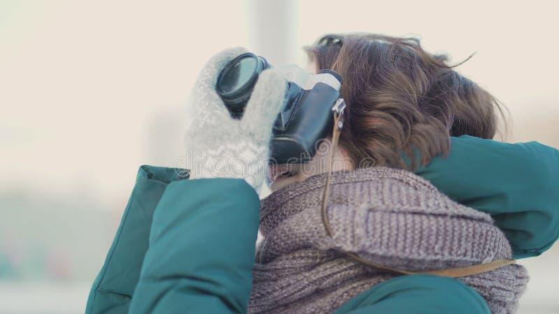 Leuke jonge vrouw die beeld nemen Mooie jonge vrouw die beelden in de stad in de winter nemen royalty-vrije stock afbeeldingen