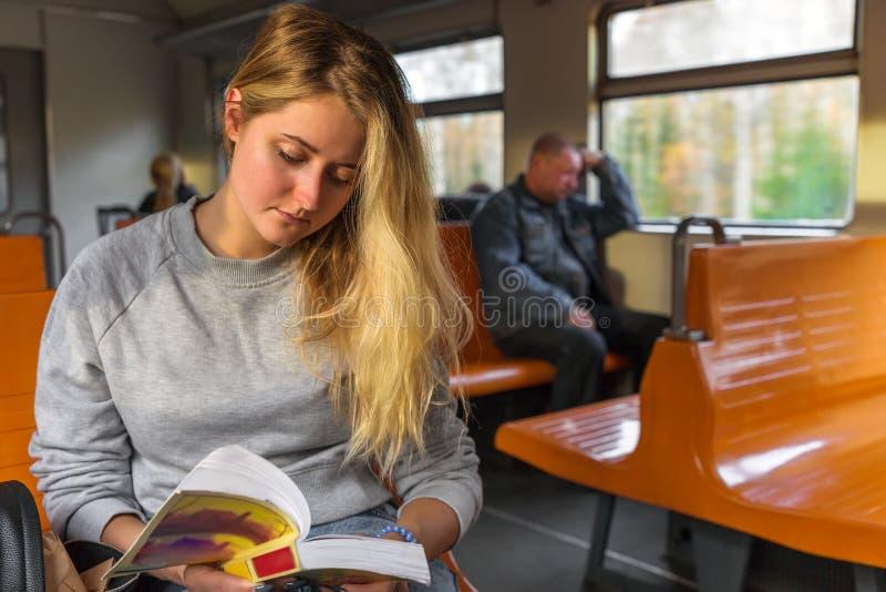 Leuke jonge vrouw die een boek met rente lezen terwijl in de trein stock afbeelding