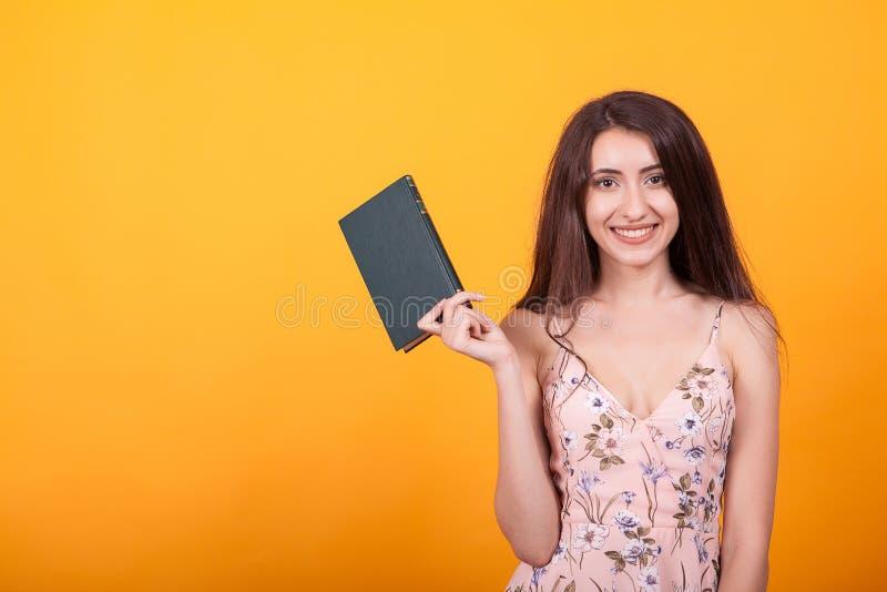 Leuke jonge vrouw die een rood boek in studio over gele achtergrond houden royalty-vrije stock foto