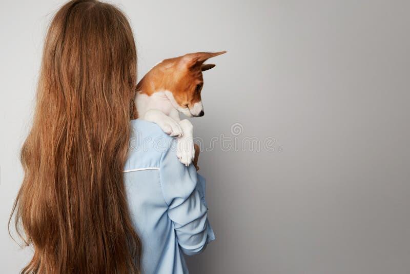 Leuke jonge vrouw die en haar hond van puppybasenji koesteren kussen Liefde tussen hond en eigenaar Geïsoleerdj op witte achtergr royalty-vrije stock foto