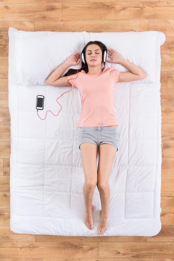 Leuke jonge vrouw die en op bed liggen slapen royalty-vrije stock afbeelding