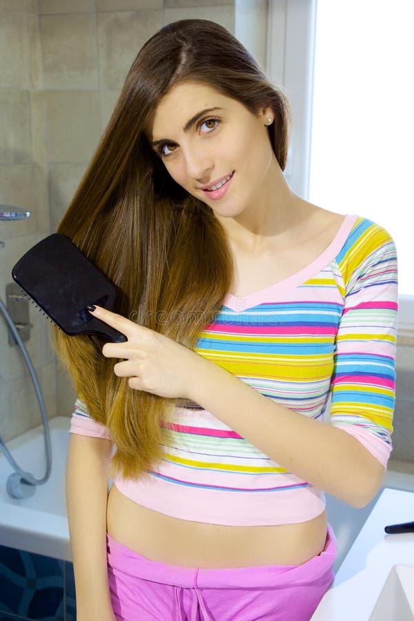 Leuke jonge vrouw die het lange haar glimlachen borstelen royalty-vrije stock fotografie