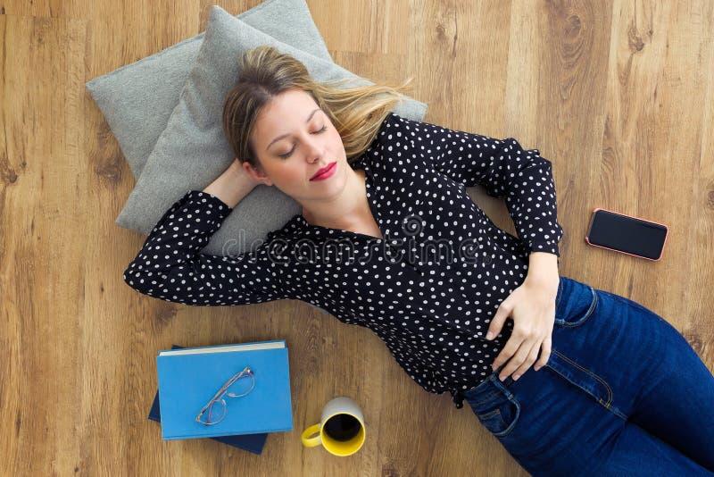 Leuke jonge vrouw die op vloer naast boeken, mobiele telefoon en koffie liggen stock afbeelding