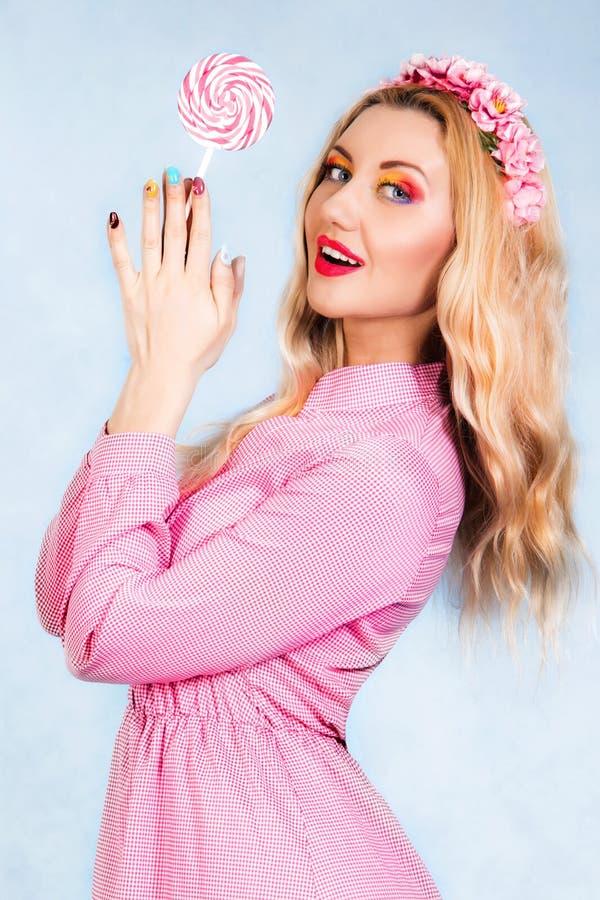 Leuke jonge vrouw in een roze kleding die een suikergoed houden stock afbeelding