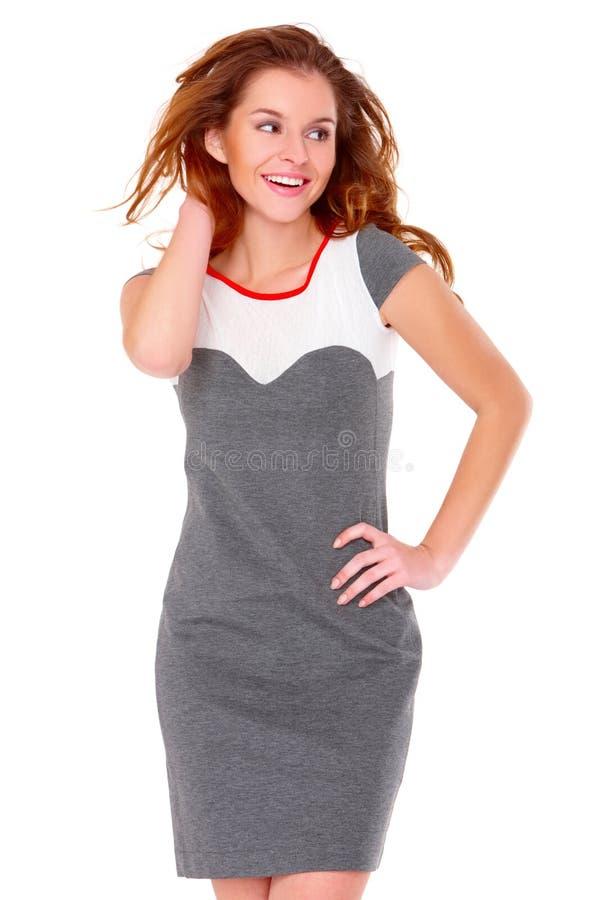 Leuke jonge vrouw in grijze kleding op wit stock fotografie