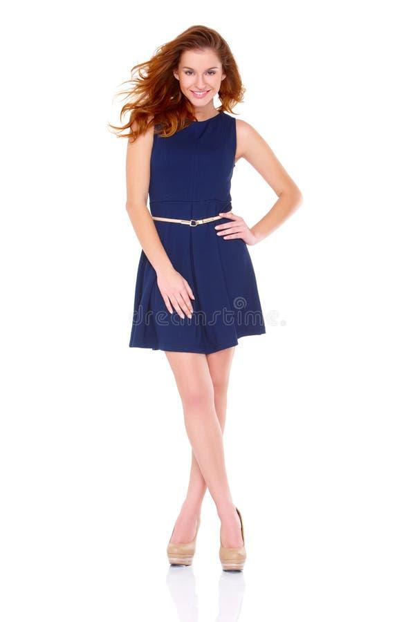 Leuke jonge vrouw in marineblauwe kleding op wit stock afbeeldingen