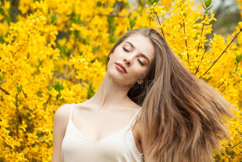 Leuke jonge vrouw in openlucht De lentemeisje met lang haar tegen bloemenachtergrond royalty-vrije stock afbeelding