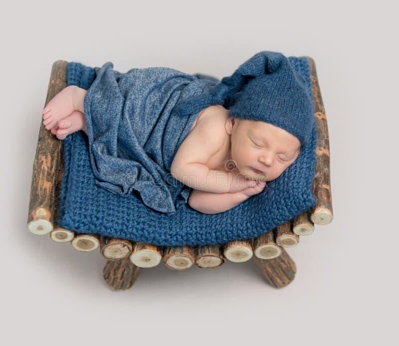 Leuke jongen in blauwe bonnetslaap royalty-vrije stock afbeelding