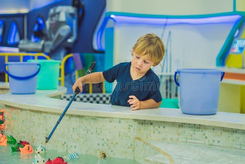 Leuke jongen in de speelkamer visserij De ontwikkeling van fijn motorconcept Het concept van het creativiteitspel royalty-vrije stock afbeeldingen