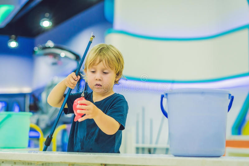 Leuke jongen in de speelkamer visserij De ontwikkeling van fijn motorconcept Het concept van het creativiteitspel stock foto's
